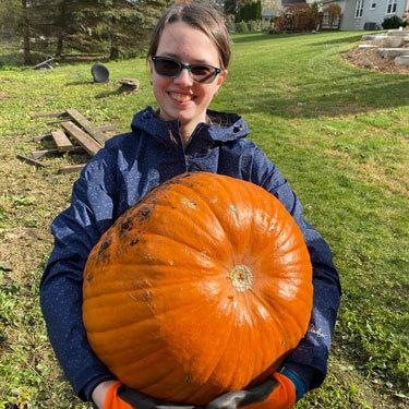 Danielle holding a giant pumpkin